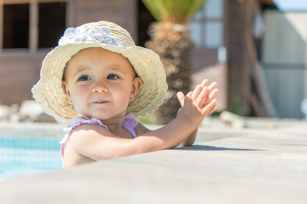 Baby mit hut im swimmingpool applaudierend Premium Fotos