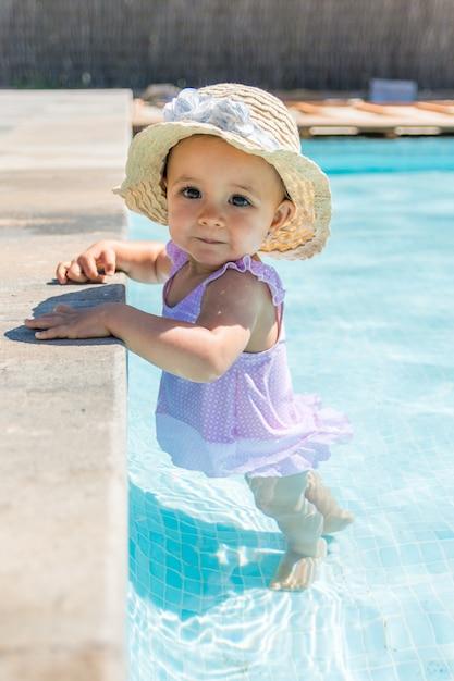 Baby mit hut in der swimmingpoolblickkamera. Premium Fotos