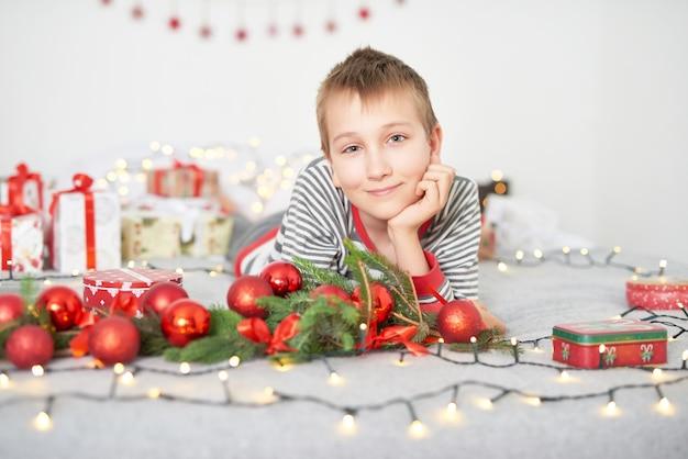 Baby mit weihnachtsgeschenken zu hause auf bett mit weihnachtsdekor Premium Fotos