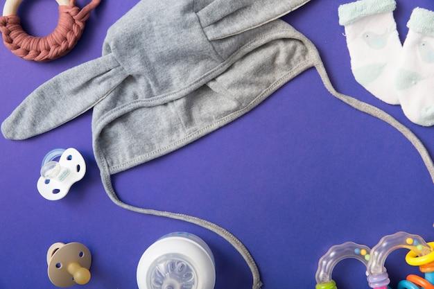 Baby mütze mit schnuller; milchflasche; spielzeug und paar socken auf blauem hintergrund Kostenlose Fotos