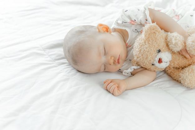 Baby schläft mit einem teddybär Kostenlose Fotos
