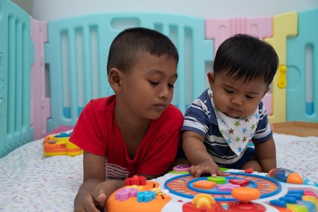 Baby-spielspielzeug mit zwei kleinen brüdern im raum Premium Fotos