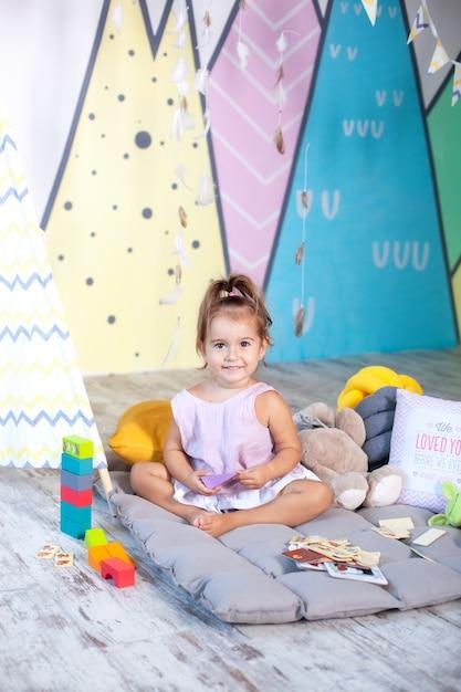 Baby spielt ein wigwam. skandinavisches interieur und textilien für den kindergarten. happy baby spielt in einem zelt in einem kinderzimmer. kleines mädchen spielt im kindergarten. kindheitskonzept, kindliche entwicklung. Premium Fotos