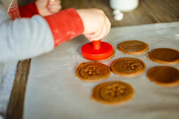Baby stempelt schneeflocken auf dem teig für lebkuchenplätzchen. Premium Fotos