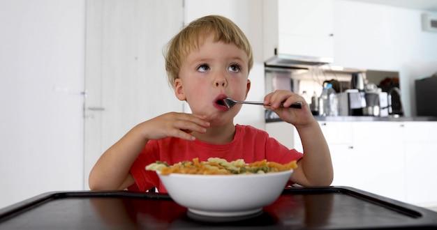Babykind, das zu hause spaghettis im wohnzimmer isst Premium Fotos