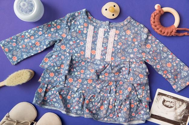 Babykleid mit milchflasche umgeben; schnuller; bürste; schuhe und ultraschallbild auf blauem hintergrund Kostenlose Fotos