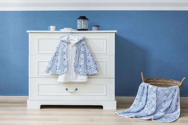 Babykleidung, die am seil auf grauem hintergrund hängt Premium Fotos
