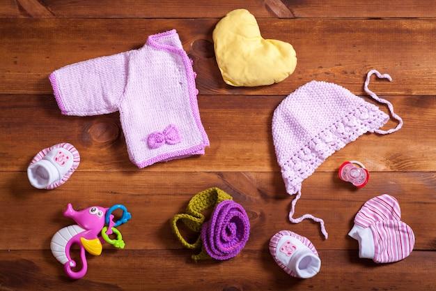 Babykleidung set-konzept, rosa strickkleidung, spielzeug und accessoires auf braunem holzhintergrund, kind neugeborenen modetuch für mädchen, modernes babypartygeschenk, babybekleidungsgeschäft, draufsicht flach legen Premium Fotos