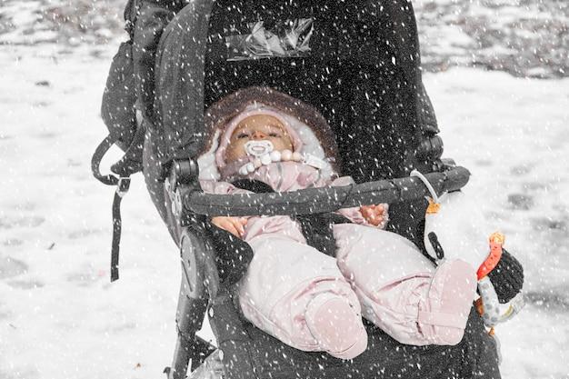 Babykleinkind im balck spaziergänger draußen an einem snowy winter dayin sonwsuit Premium Fotos