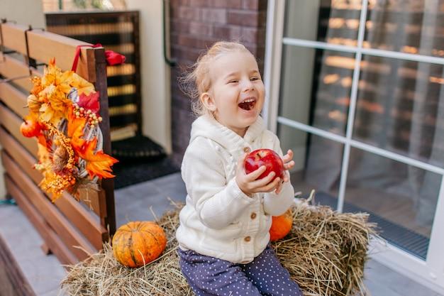 Babykleinkind in der weißen strickjacke, die auf dem heuschober mit kürbisen am portal sitzt, mit apfel spielt und lacht Premium Fotos