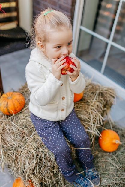 Babykleinkind in der weißen strickjacke, die auf dem heuschober mit kürbisen am portal sitzt und apfel isst. Premium Fotos