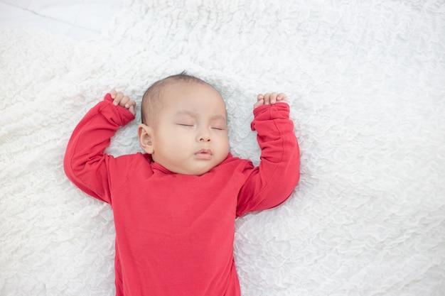 Babys, welche die roten hemden schlafen im bett tragen Kostenlose Fotos
