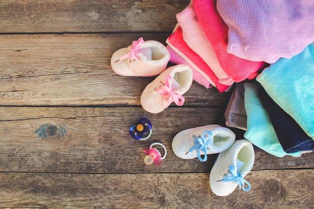 Babyschuhe, kleidung und schnuller rosa und blau auf dem alten holz Premium Fotos