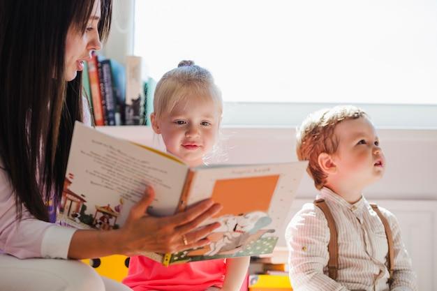 Babysitter zeigt buch zu mädchen Kostenlose Fotos