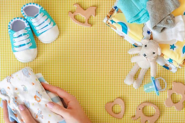 Babyzubehör für neugeborene auf einem farbigen hintergrund. Premium Fotos
