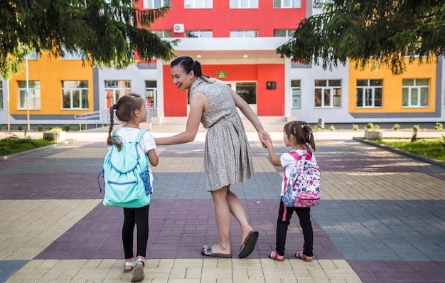 Back to school bildungskonzept mit mädchen, grundschülern, rucksäcken zum unterricht tragend Premium Fotos