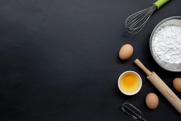 Backen kochen zutaten auf schwarzem hintergrund. draufsicht Premium Fotos