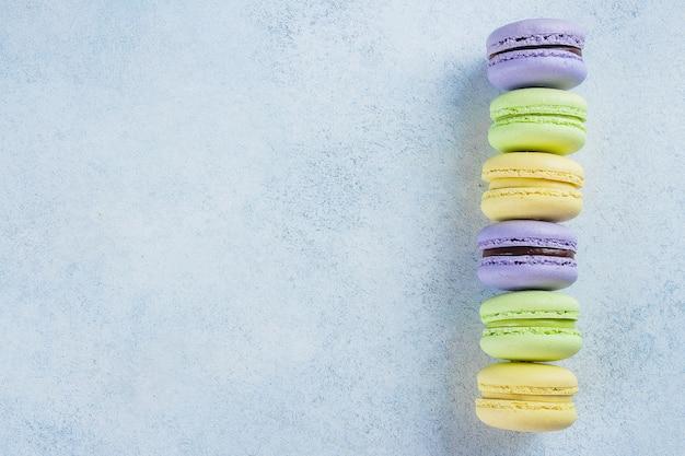Backen sie macaron oder makrone auf hellblauem hintergrund von oben zusammen Premium Fotos