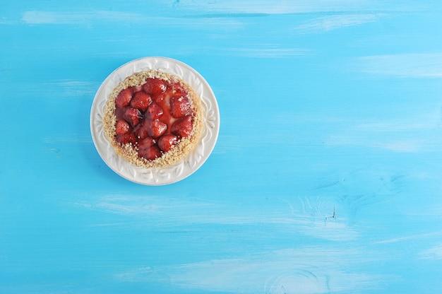 Backen sie mit erdbeeren und gelee auf einem blauen hölzernen zusammen Premium Fotos