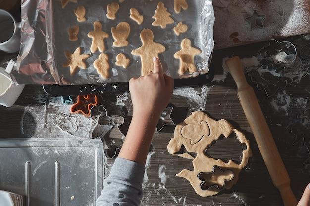 Backen von weihnachtsplätzchen auf dunkelbraunem holztisch. familie, die lebkuchenmann macht, kekse des lebkuchenteigs schneidend, ansicht von oben. Premium Fotos