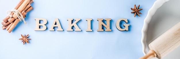 Backenkonzept mit weißer backform, nudelholz, gewürz für das backen, auf einem hellblauen hintergrund, draufsichtkopien-raumfahne Premium Fotos