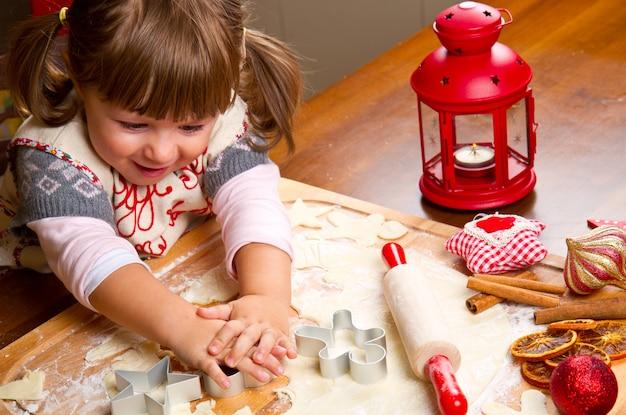 Backenweihnachtsplätzchen des kleinen mädchens, die gebäck mit einem cooki schneiden Premium Fotos