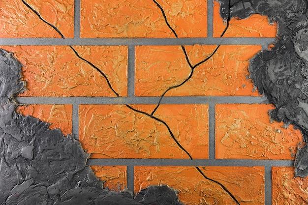 Backsteinmauer mit den sprüngen, die durch wand spähen Premium Fotos