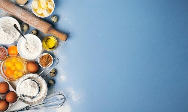Backzutaten für teig auf blau, draufsicht auf mehl, eier, butter, zucker und küchenutensilien für hausgemachtes backen mit kopierraum für text Premium Fotos