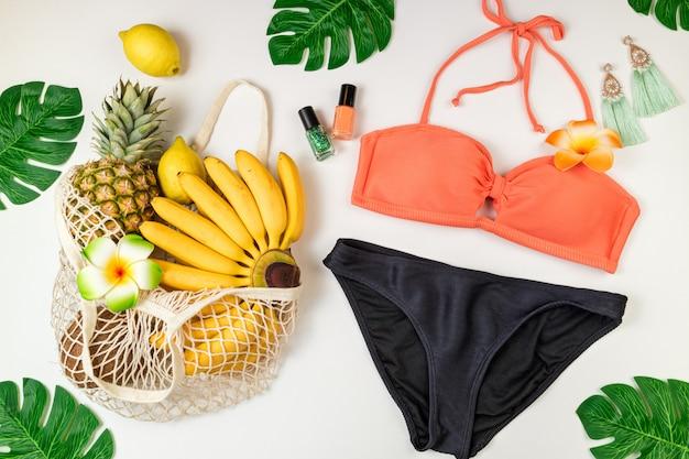 Badeanzug für strandzubehör der frau im sommerhintergrund, tropische früchte in der öko-tasche, palmblätter auf weiß Premium Fotos