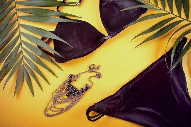 Badeanzug, halskette und tropische palmblätter aus schwarzem samt im bikini Premium Fotos