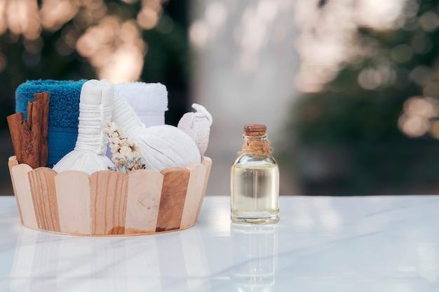 Badekurortbehandlungen stellten in hölzernen eimer mit komprimierendem kräuterball, ölflasche, kerzen und tuch auf marmorplattentabelle ein Premium Fotos