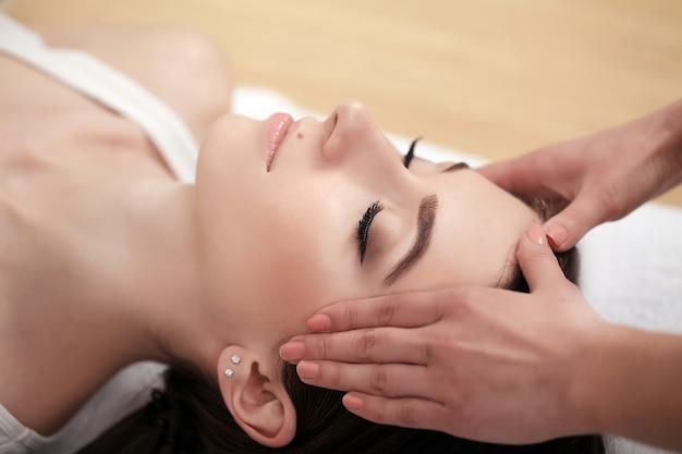 Badekurortentspannung, hautpflege, gesundes vergnügenskonzept, frau, die mit den geschlossenen augen haben entspannende gesichtsmassage liegt Premium Fotos