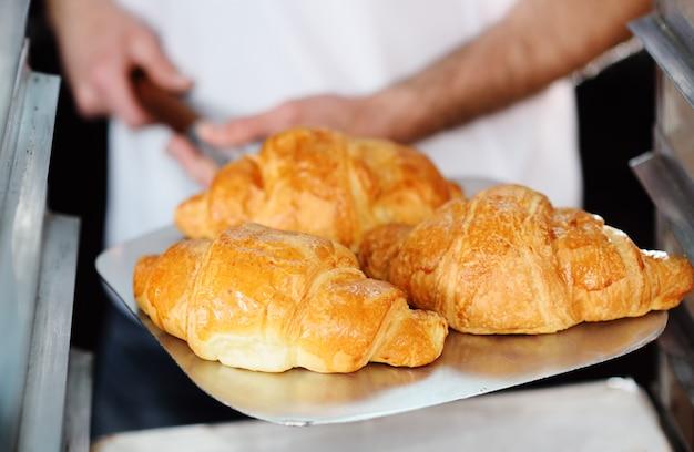 Bäcker, der ein tellersegment mit frisch gebackenen französischen hörnchen nah oben anhält Premium Fotos