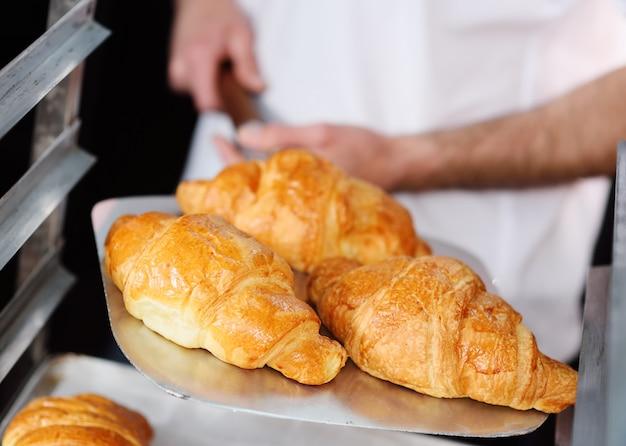 Bäcker, der ein tellersegment mit frisch gebackener nahaufnahme der französischen hörnchen anhält Premium Fotos