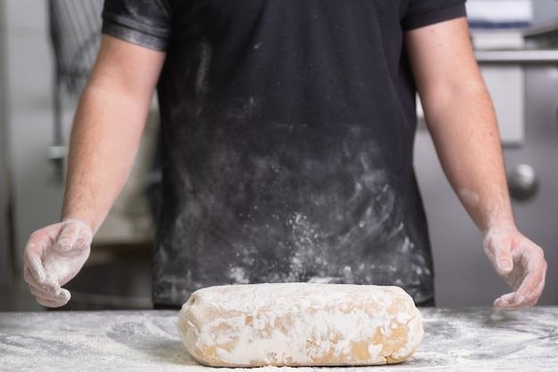 Bäcker, der frischen teig des rohen brotes an der bäckerei knetet. Premium Fotos