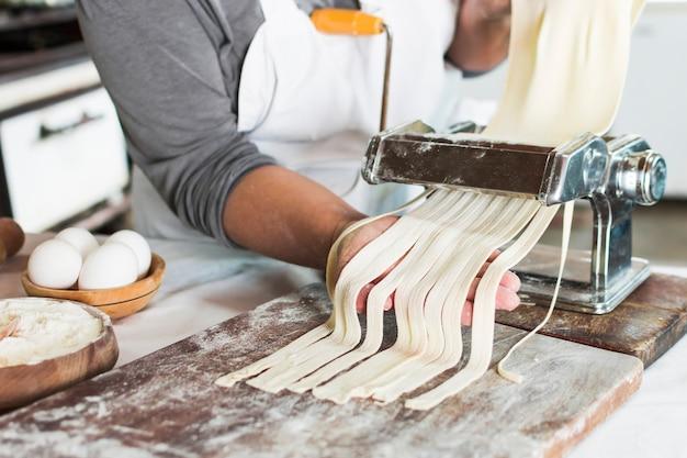 Bäcker, der rohen teig in bandnudeln auf teigwarenmaschine über dem hölzernen brett schneidet Kostenlose Fotos