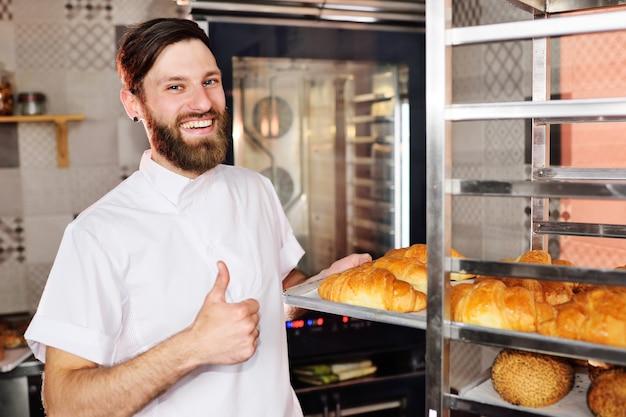 Bäcker in weißer uniform hält ein tablett mit frisch gebackenen croissants in den händen Premium Fotos
