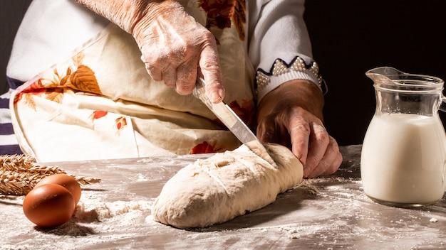 Bäcker machen muster auf rohem brot mit einem messer, um den teig vor dem backen zu formen. herstellungsprozess von spanischem brot. lebensmittelkonzept Premium Fotos