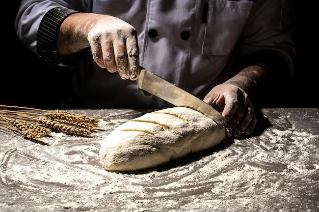 Bäcker machen muster auf rohem brot mit einem messer, um den teig vor dem backen zu formen Premium Fotos