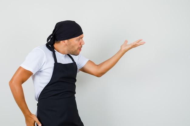 Bäcker mann im t-shirt, schürze, die fragen gestikulierend macht und wütend aussieht Kostenlose Fotos