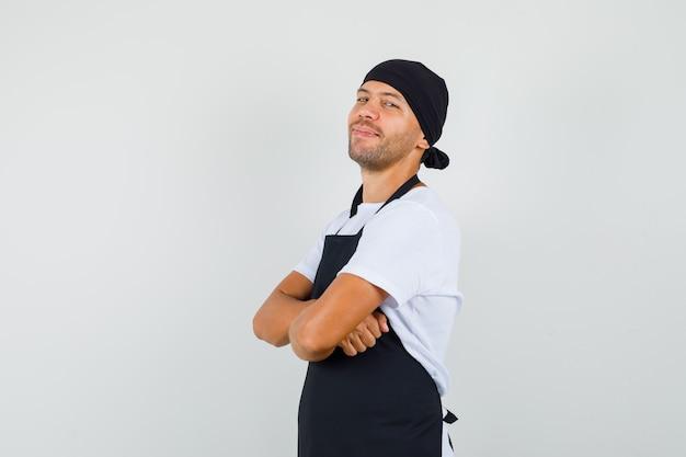 Bäcker mann im t-shirt, schürze mit verschränkten armen stehend und fröhlich aussehend Kostenlose Fotos
