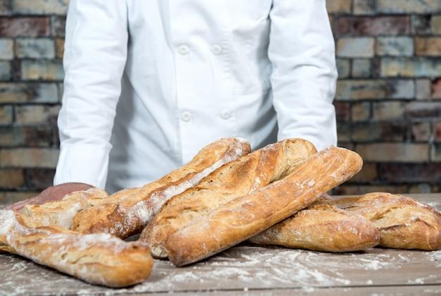 Bäcker mit französischem baguette des traditionellen brotes Premium Fotos