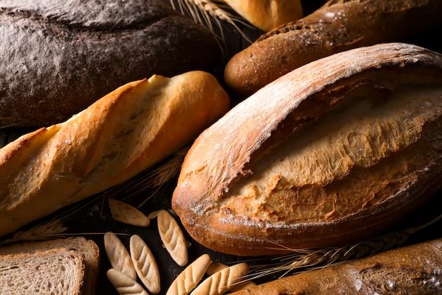 Bäckerei - goldrustikale knusprige brotlaibe und brötchen auf schwarzem tafelhintergrund. Premium Fotos