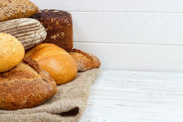 Bäckereihintergrund, brotsortiment. roggenbrötchen und draufsicht der französischen baguettes Premium Fotos