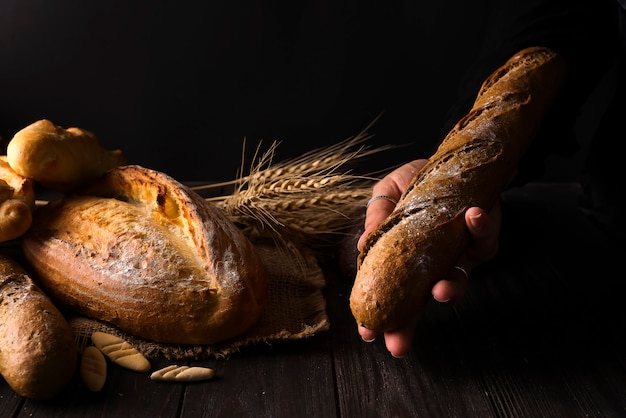 Bäckerfrau, die rustikalen organischen brotlaib in den händen hält Premium Fotos