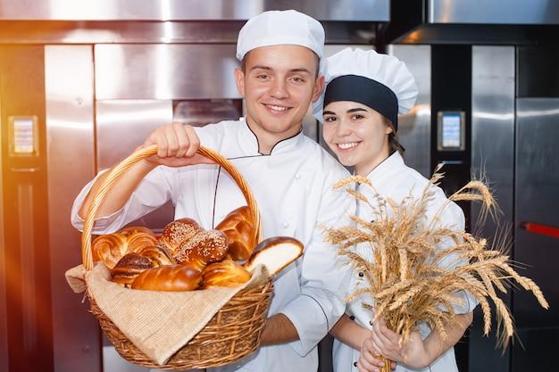 Bäckerjunge und -mädchen mit einem backenkorb und ährchen Premium Fotos