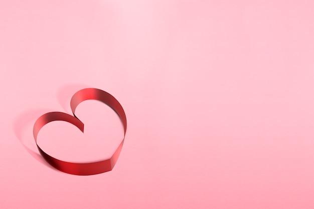Bänder geformt als herzen über rosa hintergrund Premium Fotos