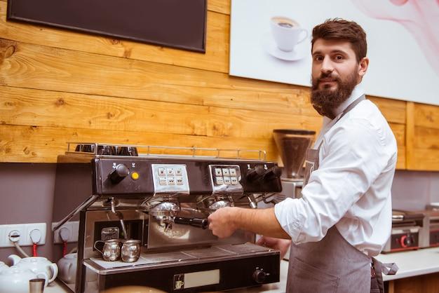 Bärtiger barista macht kaffee für einen kunden. Premium Fotos