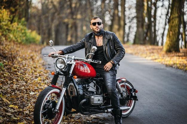 Bärtiger brutaler mann in sonnenbrille und lederjacke, der auf einem motorrad auf der straße im wald sitzt Premium Fotos