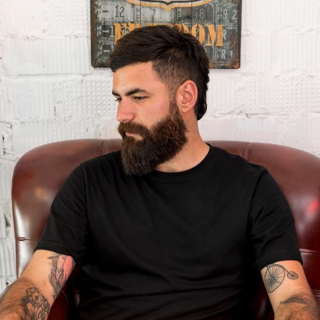 Bärtiger friseur, der auf stuhl am friseursalon sitzt Kostenlose Fotos